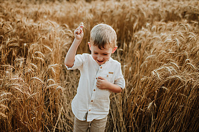 Boy gesturing while standing in wheat field - p300m2206720 by Gala Martínez López