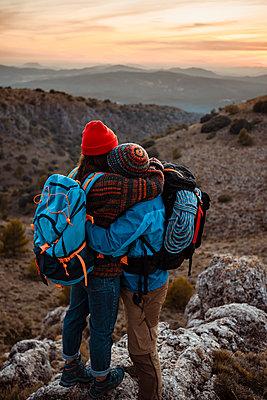 Couple embracing while standing on mountain peak during sunset - p300m2241226 by Rafa Cortés