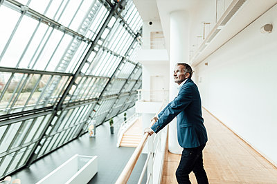 Thoughtful businessman looking away while leaning on railing in office corridor - p300m2265688 by Gustafsson