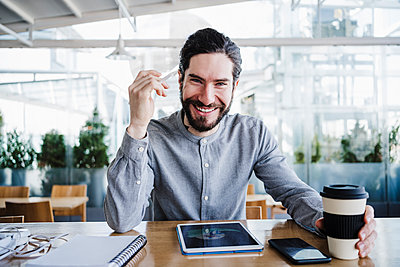 Smiling male freelancer with reusable coffee cup by wireless technologies in office - p300m2274596 by Eva Blanco