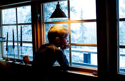 Boy looking out of a window - p312m1131409f by Peter Lyden
