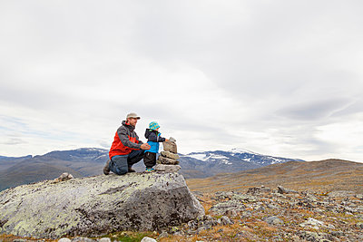 Male hiker with son building cairn in mountain landscape, Jotunheimen National Park, Lom, Oppland, Norway - p429m1561716 by Tiina & Geir