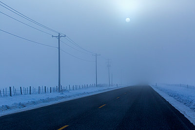 Full moon over road in winter - p555m1232045 by Steve Smith