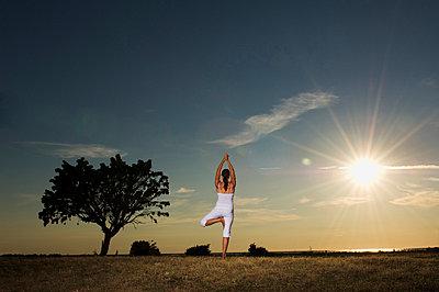 A woman doing yoga, Gotland, Sweden. - p5755345f by Hans Berggren