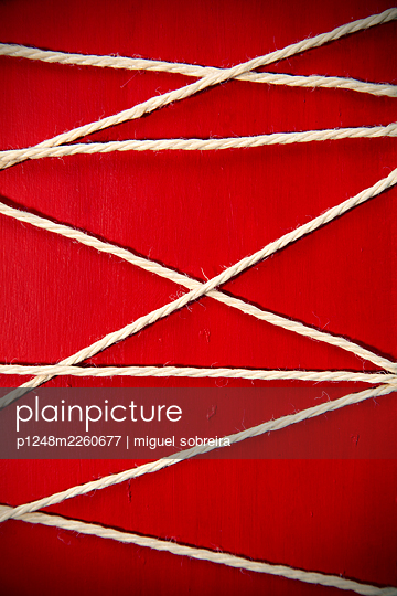 Cord against red background - p1248m2260677 by miguel sobreira