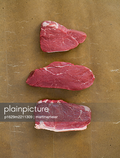 Three pieces of meat against brown background - p1629m2211309 by martinameier.ch