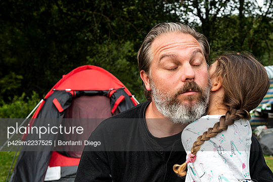 Girl hugging her dad at camp site - p429m2237525 by Bonfanti Diego