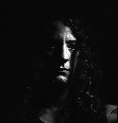Selbstportrait eines langhaarigen jungen Mannes in Schwarz-weiß - p1180m1020401 von chillagano