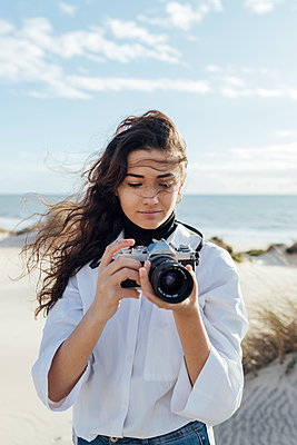 Young woman taking pictures with analogic camera in the beach, Matalascañas, Huelva, Spain - p300m2253026 von Julio Rodriguez
