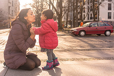Mother kissing daughter on pavement - p429m2091768 by Tamboly