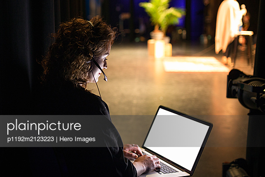 Female event coordinator using laptop backstage - p1192m2123223 by Hero Images