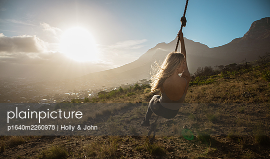 Blond woman swings on rope at sunset - p1640m2260978 by Holly & John