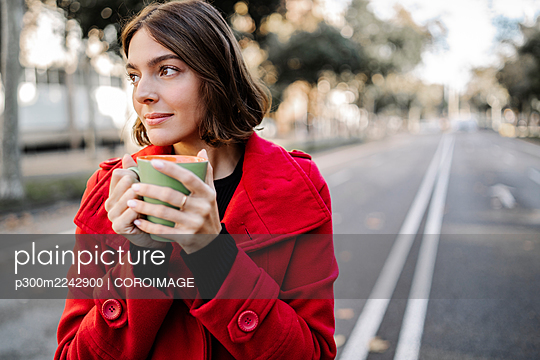 Thoughtful young woman in red jacket holding coffee cup on street - p300m2242900 by COROIMAGE