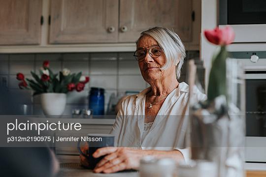 Smiling woman having coffee - p312m2190975 by Jennifer Nilsson