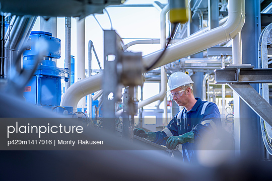 Worker with process machinery in oil blending factory - p429m1417916 by Monty Rakusen