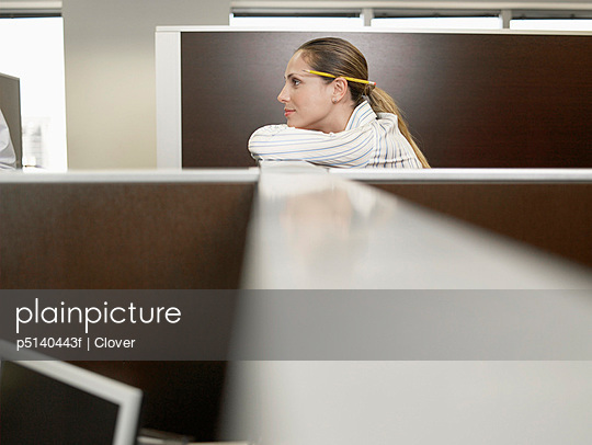 Office worker leaning against partition wall
