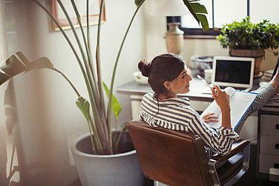 Businesswoman reading paperwork with feet up on desk - p1023m1520011 by Paul Bradbury