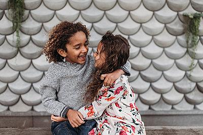 Cute siblings smiling and laughing at each other while hugging outside - p1166m2163421 by Cavan Images