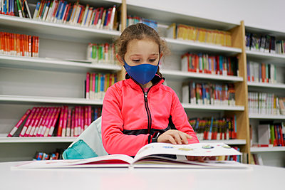 Little girl wearing a medical mask and reading a book in a libra - p1166m2232514 by Cavan Images