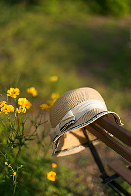 Ladies straw summer hat hung up over the back of a chair in a garden. - p1433m1578240 by Wolf Kettler