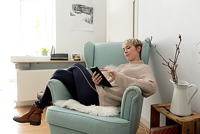 Relaxed woman sitting in armchair at home using tablet - p300m2103004 by FL photography