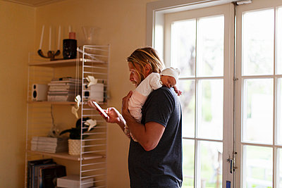 Sweden, Father holding newborn son (0-1 months) and looking at smartphone - p352m1187016 by Christian Ferm