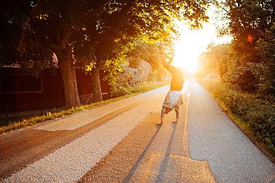Man doing a handstand on a road at sunset in Bohuslan, Sweden - p352m1523656 by Benjamin Rudström