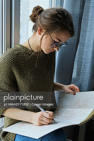 millennial girl draws fabulous images on paper while sitting at home - p1166m2171832 by Cavan Images