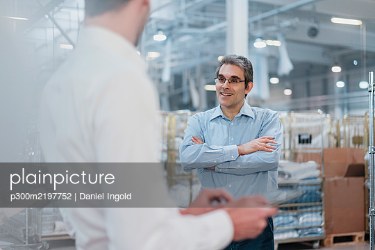 Two businessmen having a meeting in a factory - p300m2197752 by Daniel Ingold