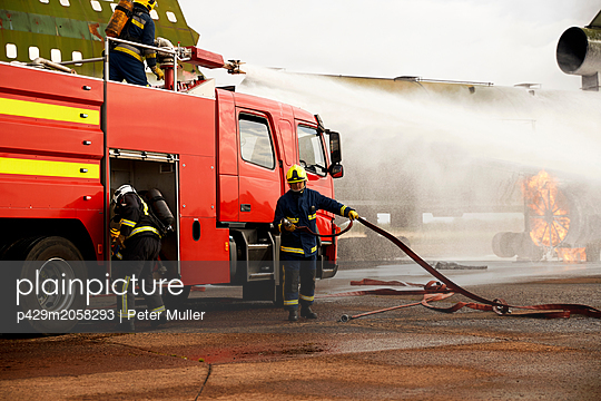 Firemen training, spraying water from fire engine at mock airplane engine - p429m2058293 by Peter Muller