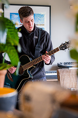 Young man playing guitar at home, stay at home due to Covid-19 - p1057m2185210 by Stephen Shepherd