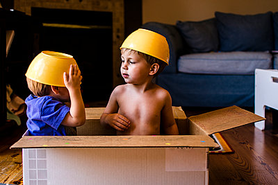 Playful brothers with bowls on head sitting in cardboard box at home - p1166m1185988 by Cavan Images