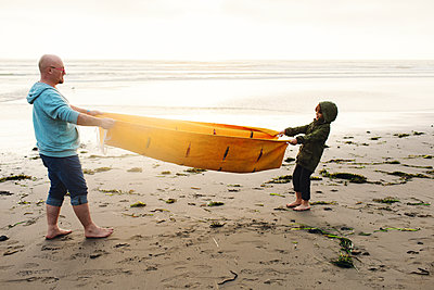 Side view of playful father and son pulling picnic blanket while standing on shore at beach against clear sky - p1166m1509693 by Cavan Images