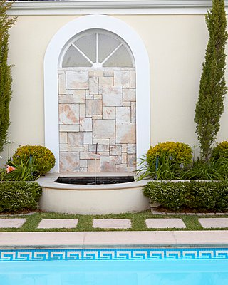 Arched window filled with mosaic of stone tiles and small fountain - p1183m997676 by Great Stock!