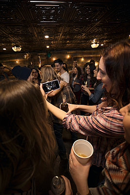 Young women friends drinking beer and taking selfie with camera phone at party - p1192m1403440 by Hero Images