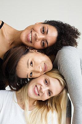 Portrait drei attraktiver, multiethnischer Frauen, die Ihre Köpfe übereinander stapeln   - p1301m2020996 von Delia Baum