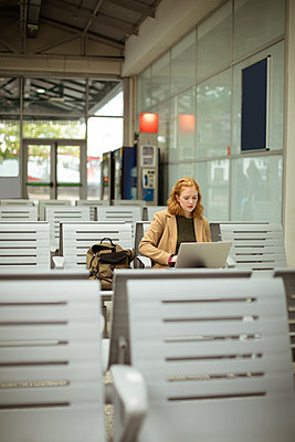 Young woman using her laptop at bus stop - p1315m1578831 by Wavebreak