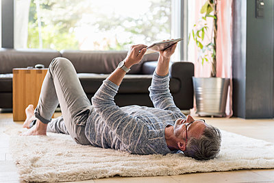 Mature man lying on carpet at home using a tablet - p300m2004696 von Daniel Ingold