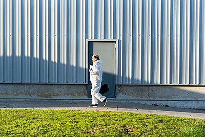 Female scientist wearing protective suit in front of a laboratory - p300m2170142 by Eloisa Ramos