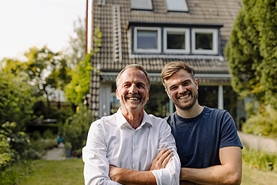 Cheerful father and son standing in backyard - p300m2276931 by Gustafsson