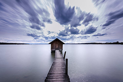 Germany, Bavaria, View of boathouse with pier at Ammersee Lake - p300m752501f by Michael Bottari