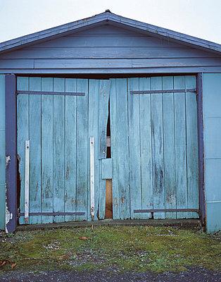 Broken blue painted wooden garage doors - p3490338 by Elsa Young