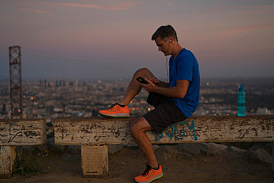Jogger sitting on bench looking at smartphone, Runyon Canyon, Los Angeles, California, USA - p924m1422788 by Raphye Alexius