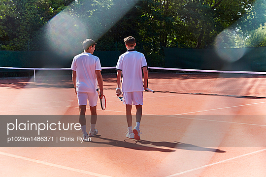 Young male tennis players walking with tennis rackets on sunny clay tennis court