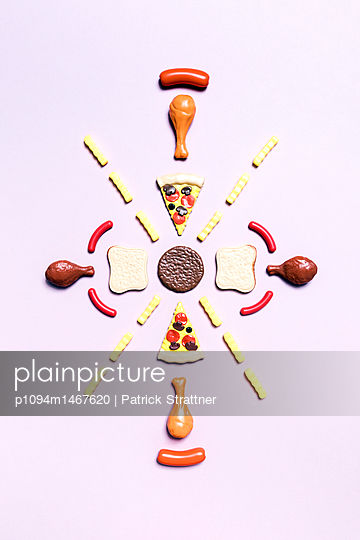 Directly above shot of various fast food toys arranged on pink background - p1094m1467620 by Patrick Strattner