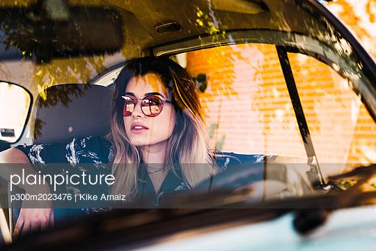 Young woman wearing sunglasses sitting in a car - p300m2023476 von Kike Arnaiz