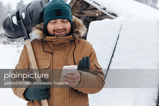 Portrait of smiling man with snow shovel looking at cell phone - p300m2167380 by Konstantin Trubavin