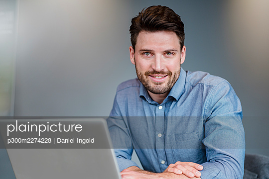 Male professional with laptop in office - p300m2274228 by Daniel Ingold