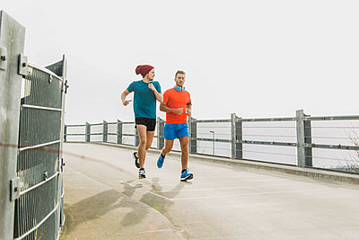 Two young men jogging on bridge - p300m1019124f by Uwe Umstätter