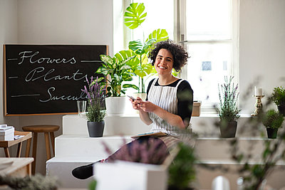 Portrait of smiling young woman using cell phone in a small shop with plants - p300m2143812 von HalfPoint